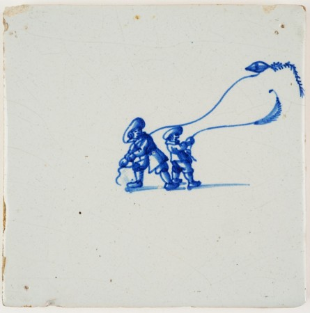 Antique Delft tile in blue with two children playing flying their kites, 17th century