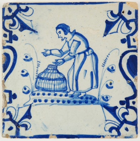 Antique Delft tile in blue with a woman about to empty a fish trap, 17th century