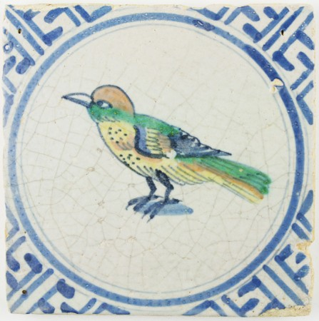 Antique Dutch Delft tile with a polychrome bird in a Wanli decorated circle motif, 17th century