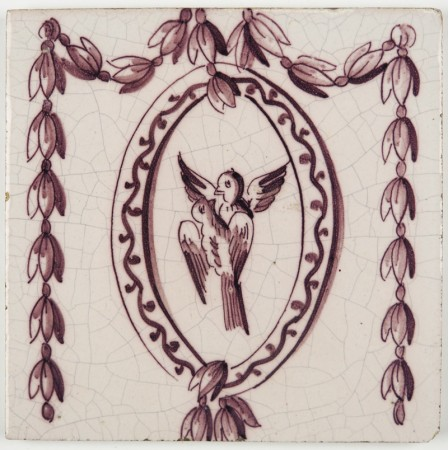 Antique Delft ornament tile with two birds in an oval shape with garlands on both sides, 19th century