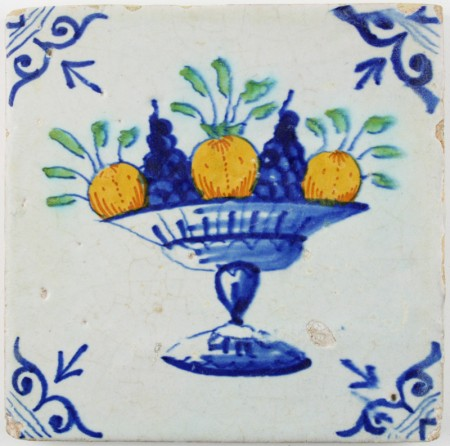 Antique Delft tile with a polychrome fruit bowl, early 17th century