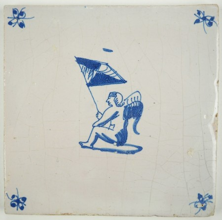 Antique Delft tile with Cupid sitting while holding a flag, late 17th century