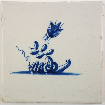 Antique Delft tile in blue with an insect flying onto fruits, 17th century