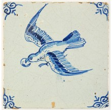Antique Delft tile in blue with a bird in flight holding a piece of fruit in its beak, 17th century