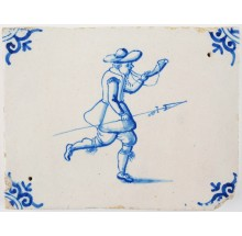Antique Delft border tile in blue with a hunter holding a spear while blowing on a horn, 17th century