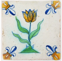 Antique Delft tile with a beautiful polychrome tulip, decorated with 'fleur-de-lis' corner motifs, 17th century