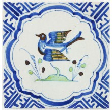 Antique Dutch Delft tile in blue with a polychrome bird in wanli corner motifs, 17th century