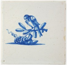 Antique Delft tile with a bird on a twig looking down om some delicious fruits, 17th century