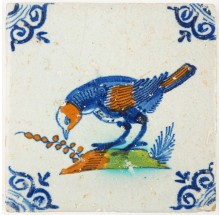 Antique Delft tile with a large polychrome bird picking seeds, 17th century