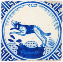 Antique Delft crown tile with a fast running dog in blue, 17th century Rotterdam