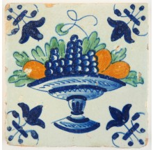 Antique Delft tile with a polychrome fruit bowl containing grapes and apples, 17th century